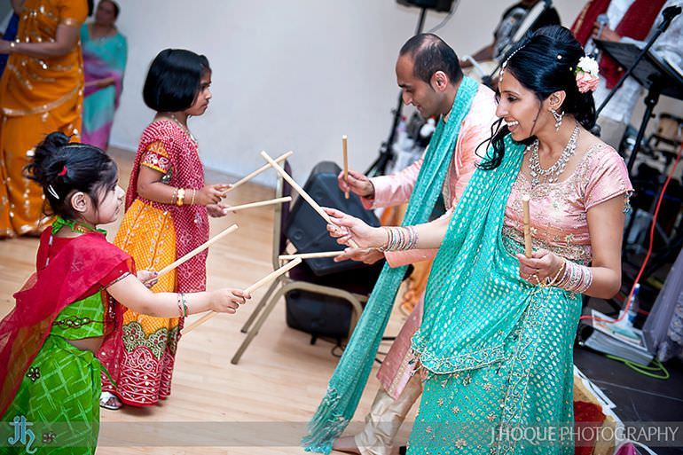 Bride and groom performing Dandia Raas with children | Sanjay Gohil Saanji in Harrow | Asian Wedding Photography London | 3433