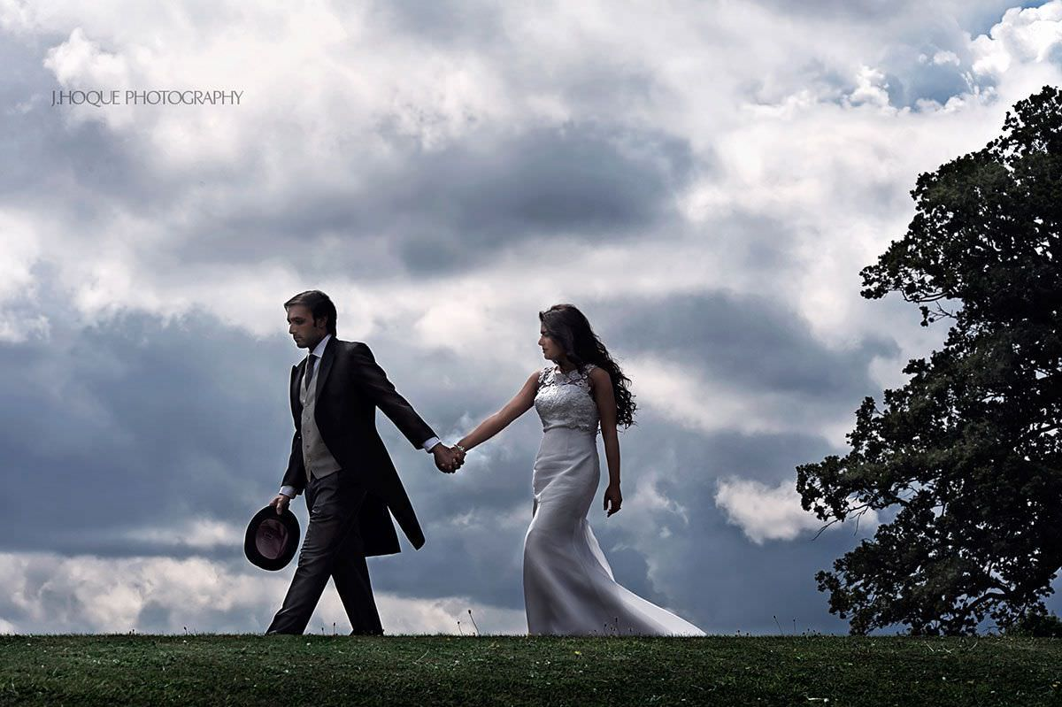 Asian bride and groom walking hand in hand at Loseley Park   Indian wedding photographer Surrey