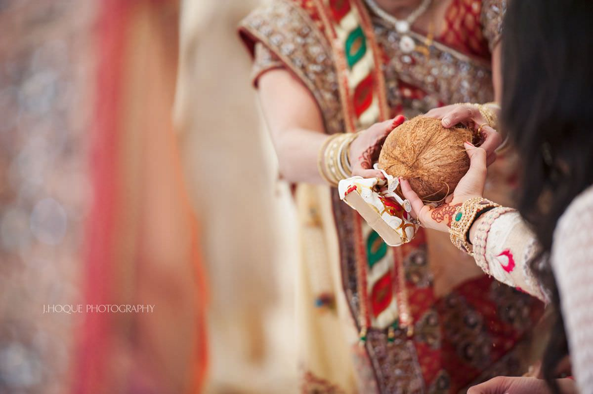 Handing over coconut | Indian wedding at Parklands Quendon Hall Essex