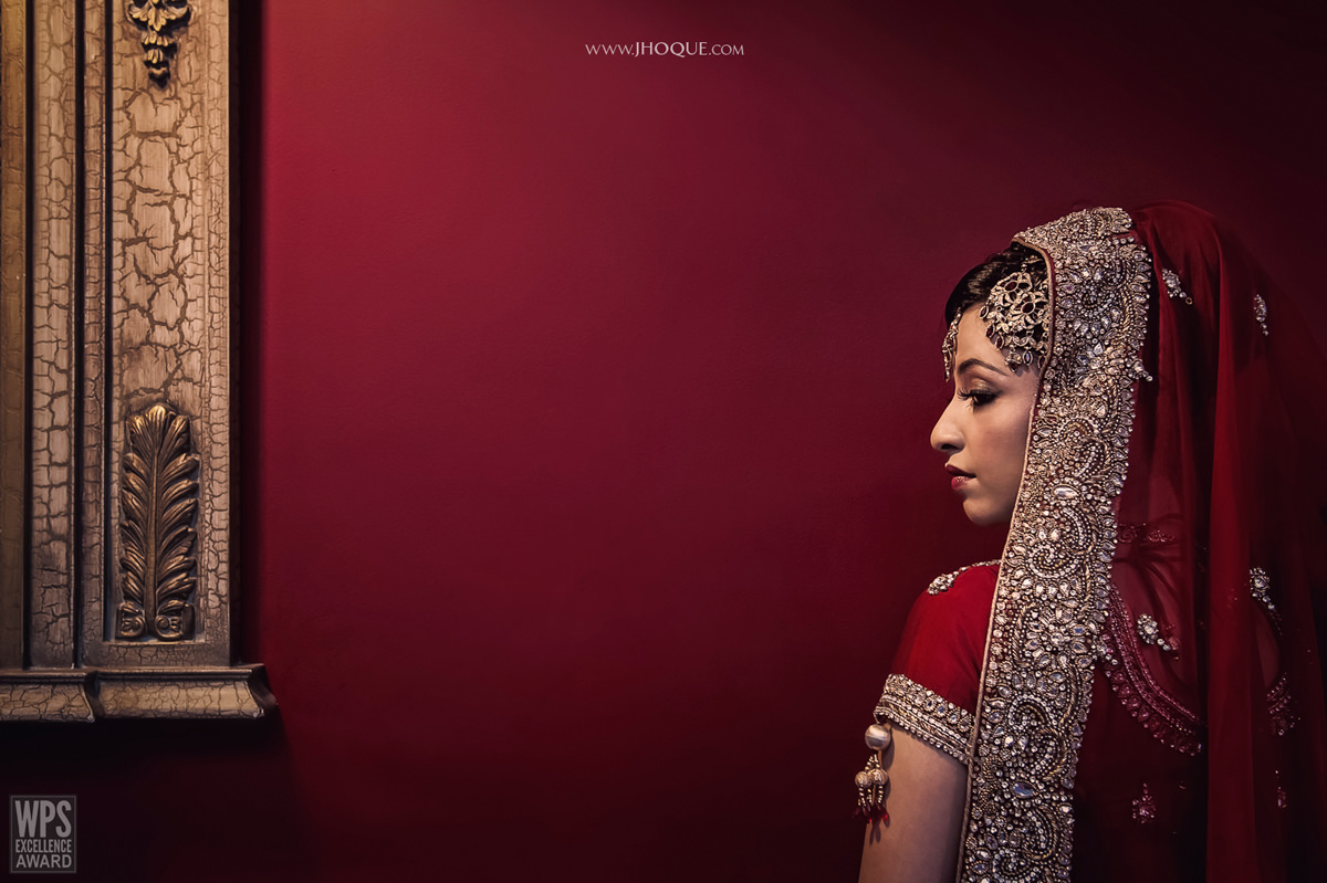 Muslim bride portrait against red wall and mirror | Asian Wedding Photography Berkshire