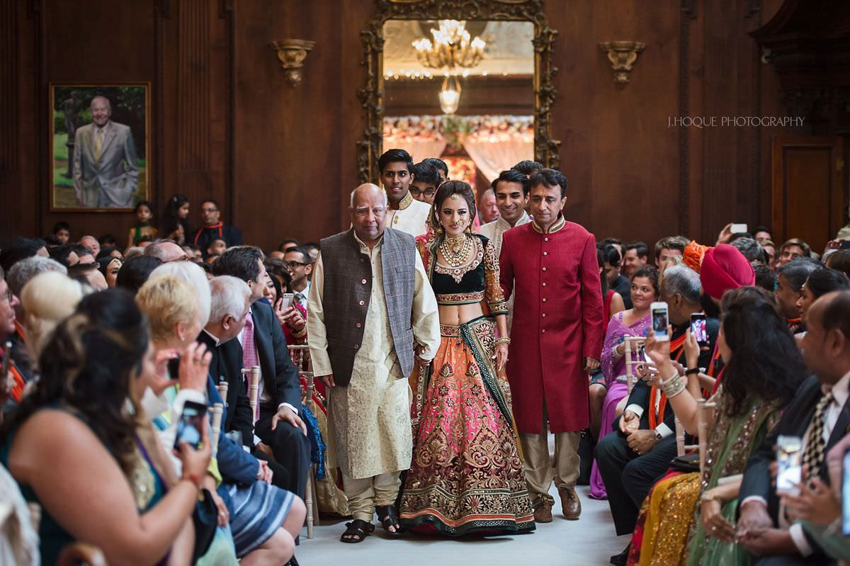 Indian bride, wearing Tarun Tahiliani wedding dress, being walked down the aisle by dad and granddad | Hindu Wedding Photographer