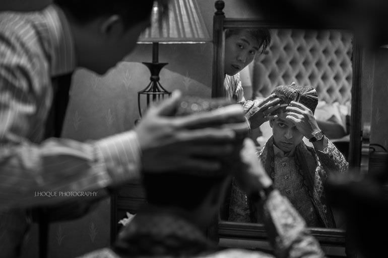 Groomsman helping groom put on Turban | Asian Wedding Photography Kent | Hever Castle | 0022-BW