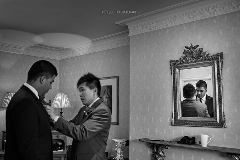 Groomsmen fixing buttonhole | Asian Wedding Photography Kent | Hever Castle | 0071-BW
