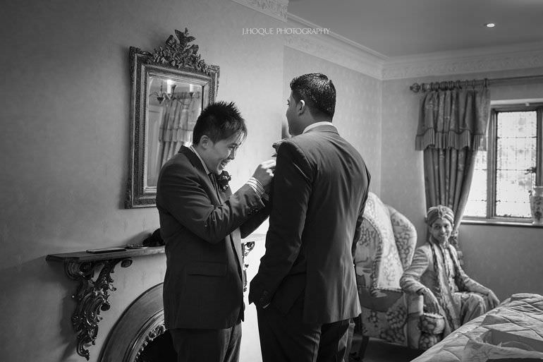 Groomsmen fixing buttonhole | Asian Wedding Photography Kent | Hever Castle | 0075-BW