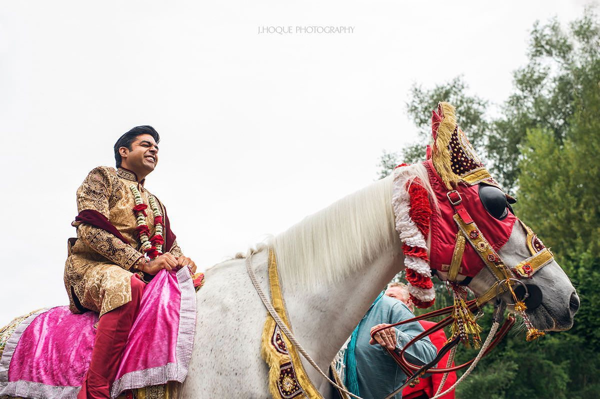 Groom making funny face on Horse | Indian wedding at Four Pillars Hotel Cotswold | Gloucestershire Wedding Photographer