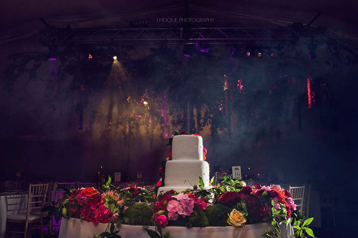 Wedding cake under creative lighting | Indian Hindu wedding at Four Pillars Gloucestershire