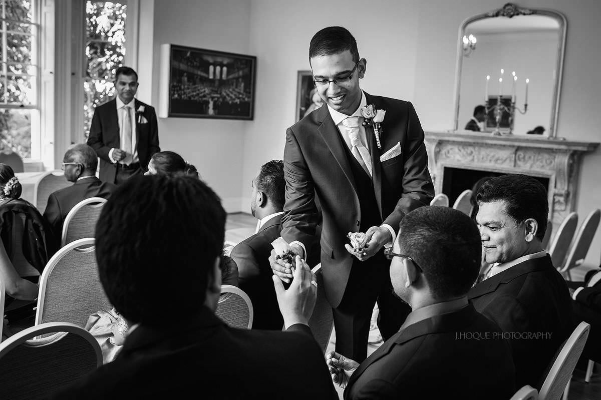 Tamil Groom handing buttonholes | Pembroke Lodge Tamil Wedding Photographer Surrey | 05