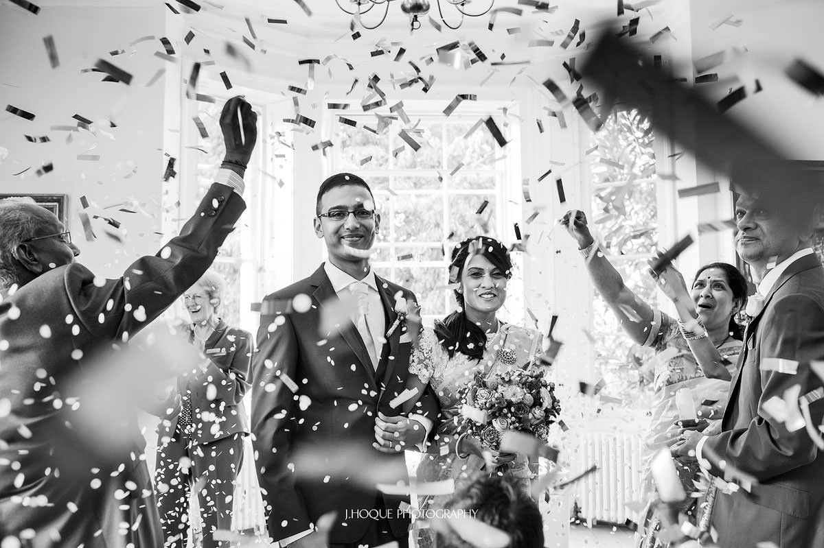 Couple showered in confetti | Pembroke Lodge Indian Wedding Surrey | 19