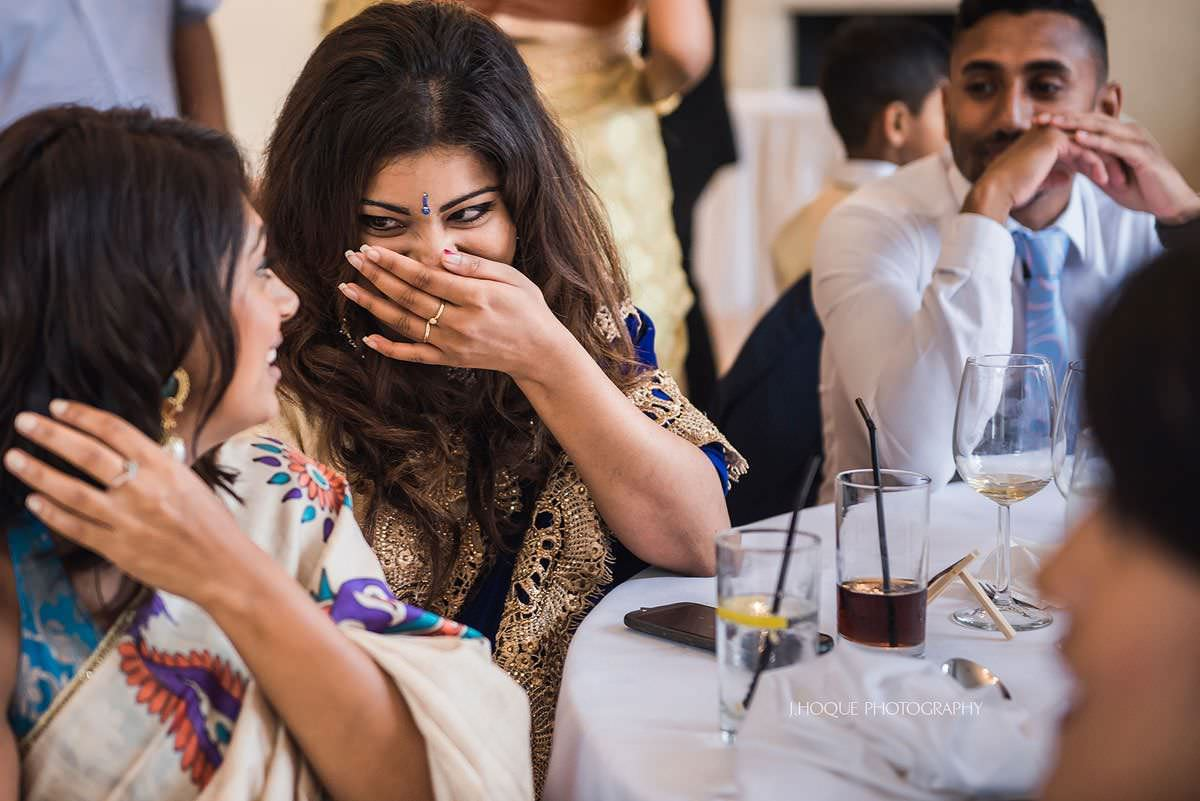 Grooms sister sharing a joke with friend | Surrey Tamil Wedding Photographer Pembroke Lodge | 28