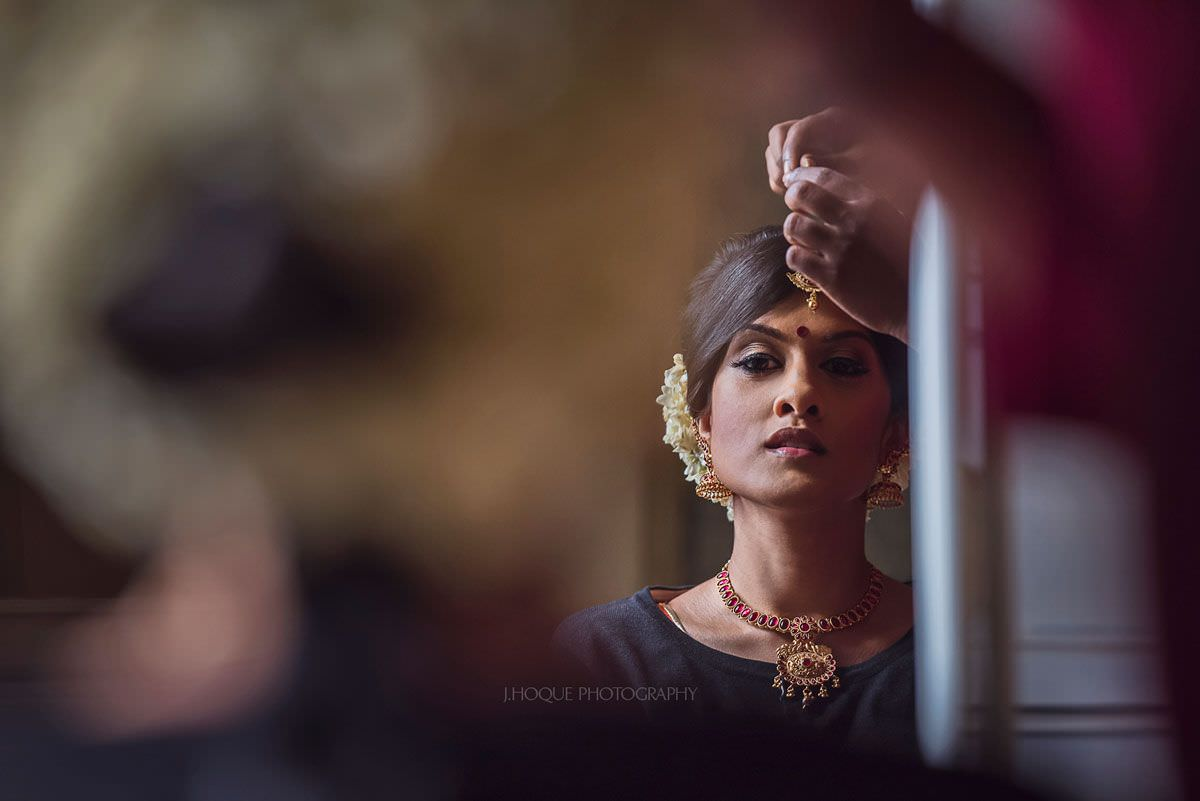 Bride putting on Tikli | Shendish Manor Tamil Wedding Hertfordshire | 05