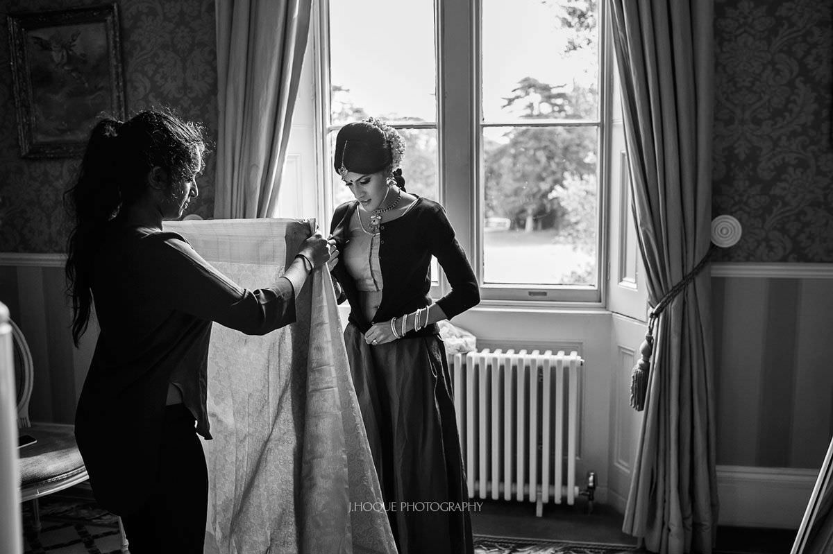 Makeup artist helping bride put on Tamil wedding saree | Hertfordshire Hindu Wedding Photographer | BW-06