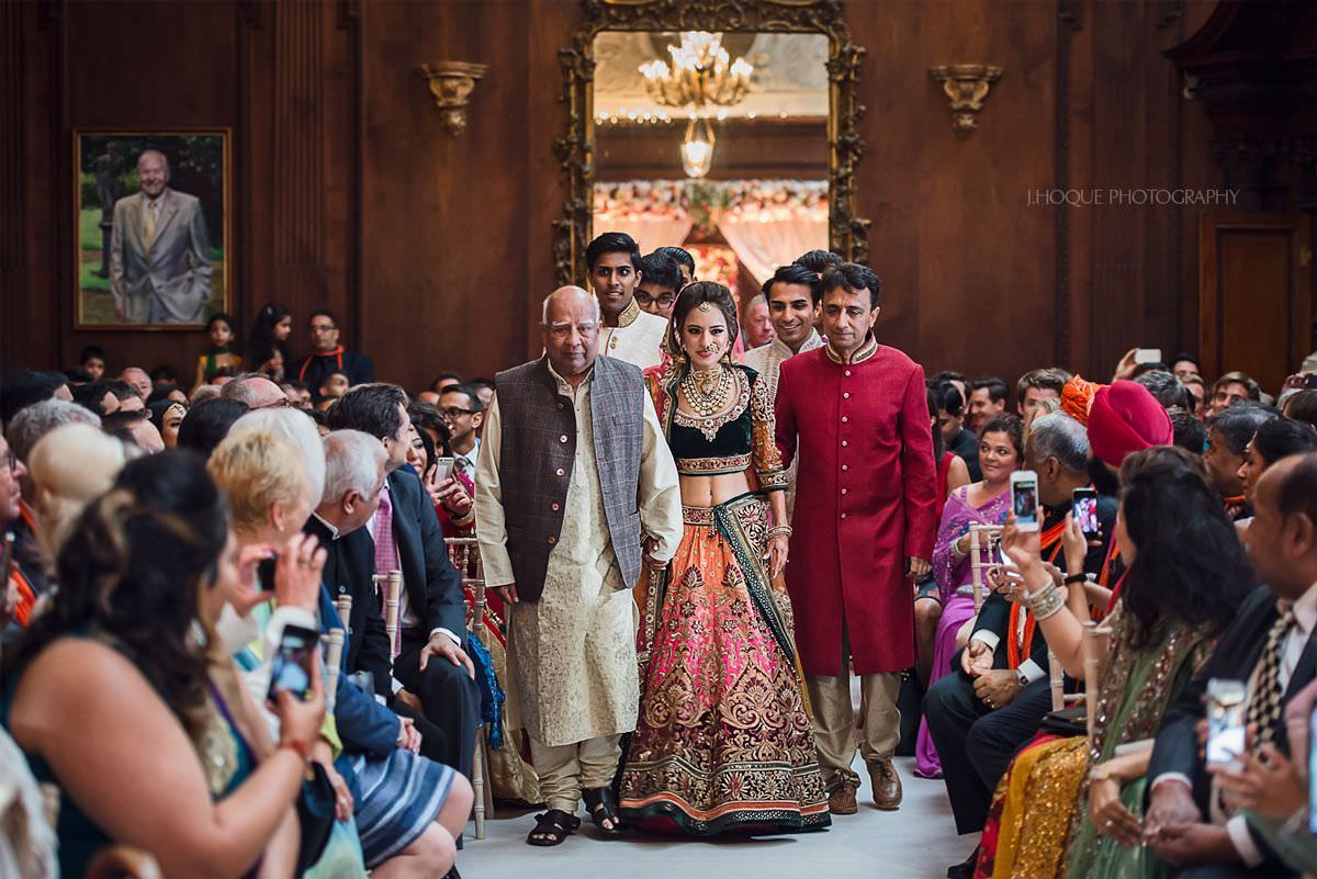 Bride's entrance with father and grandad | Luxury Asian Wedding at Thornton Manor Cheshire | 28