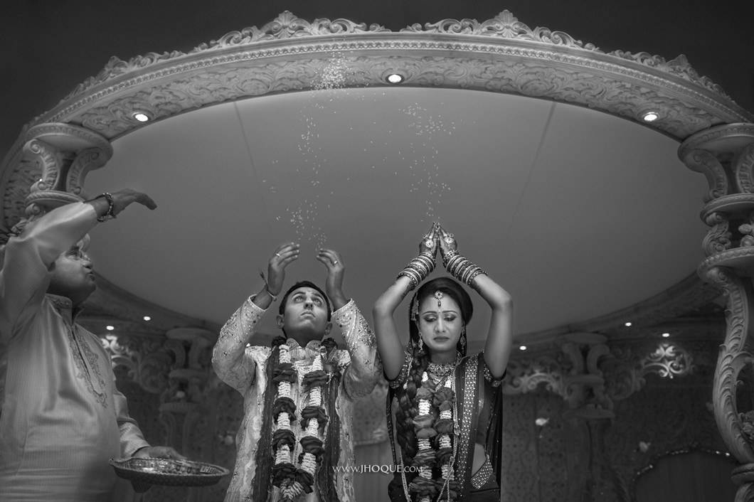 Asian bride and groom throw rice behind them in Mandap | Indian Wedding Photography London