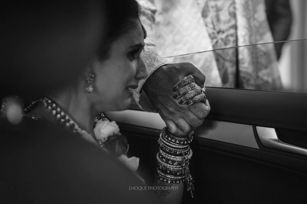 Bride holding her dads hand during vidaai | Luxury Indian Wedding Photographer London