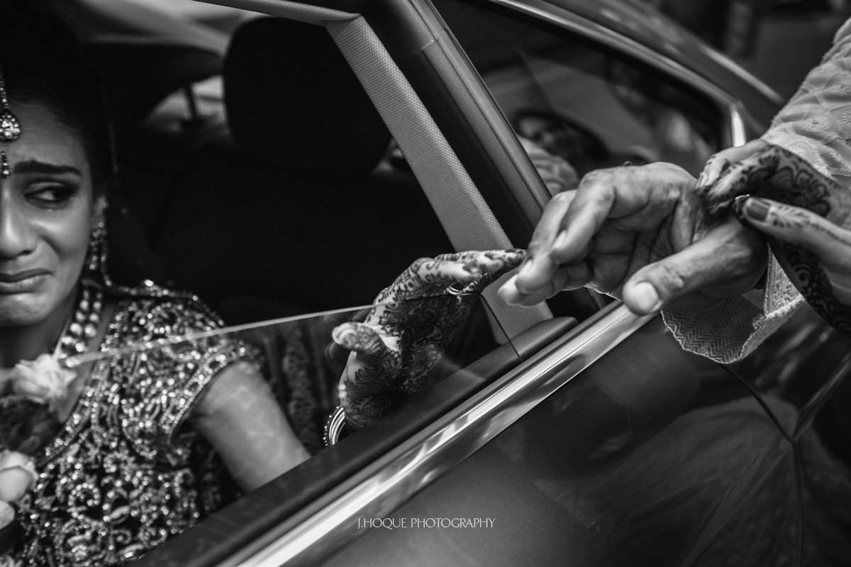 Bride reaching for parents hands during tearful vidaai | Luxury Asian Wedding at Intercontinental Park Lane London