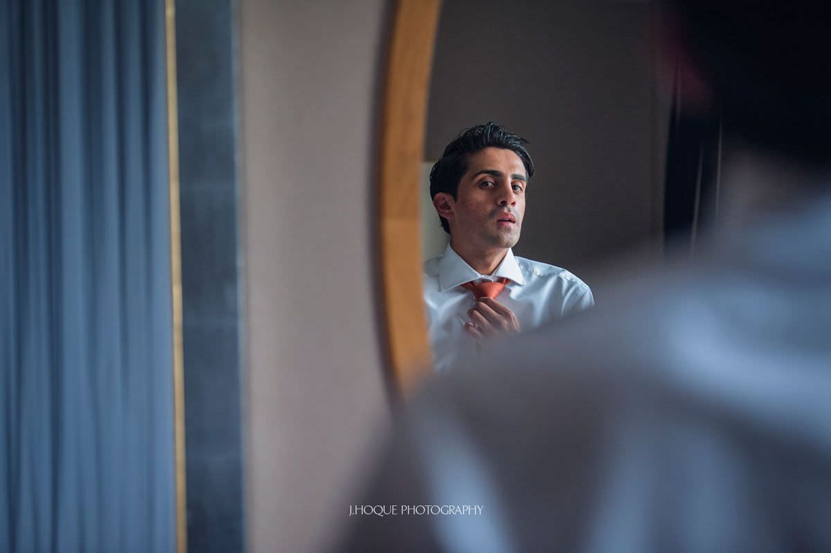 Groom looking in mirror fixing his tie | Luxury Asian Wedding at Intercontinental Park Lane London