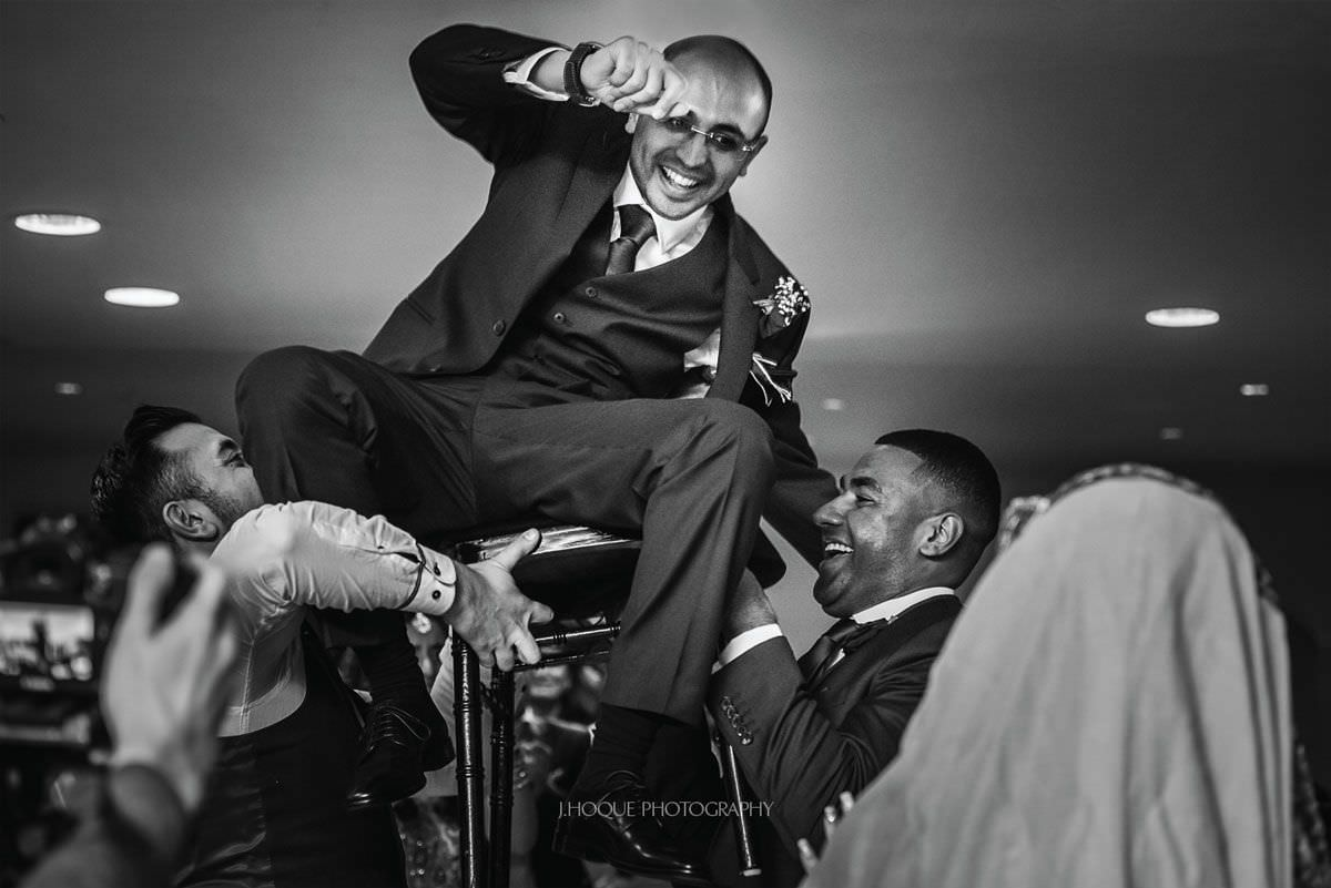 Groom lifted in air on a chair   Muslim Wedding Photography at Three Rivers Essex