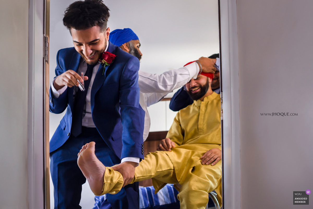 Groomsman cutting the grooms toenails | Sikh Wedding Middlesex | WPJA Award 2018 V16